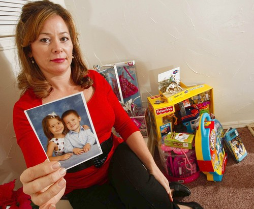 Tamera Jo Freeman holding up a photo of her beloved children. She lost them to a Communist Police State in 2009 for spanking them as any responsible parent would do.