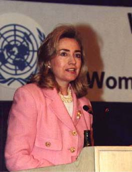 Hillary Rodham Clinton wearing pink suit giving speech at a Woman's Day conference wearing the Illuminati Phoenix Pin.